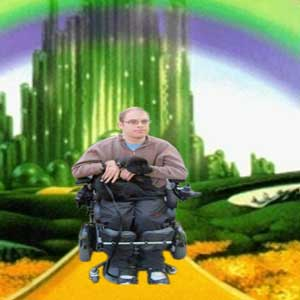 A picture of Erik driving down the yellow brick road in his wheelchair with a dog in his arms.